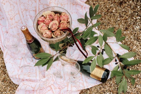Flatlay image d'un bol de roses roses, 2 bouteilles de champagne, un tapis de pique-nique rose et des feuilles d'eucalyptus