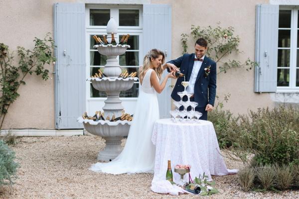Les mariés rient alors qu'ils versent du champagne dans une tour de verre à champagne à l'extérieur du château lacanaud