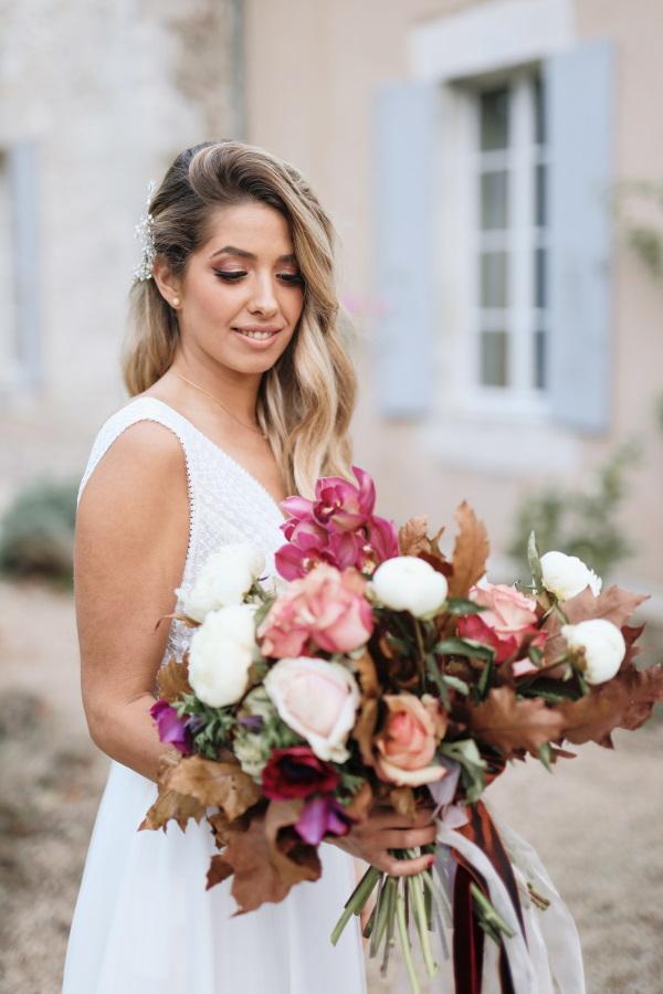 La mariée sourit et regarde le bouquet de fleurs bordeaux et roses