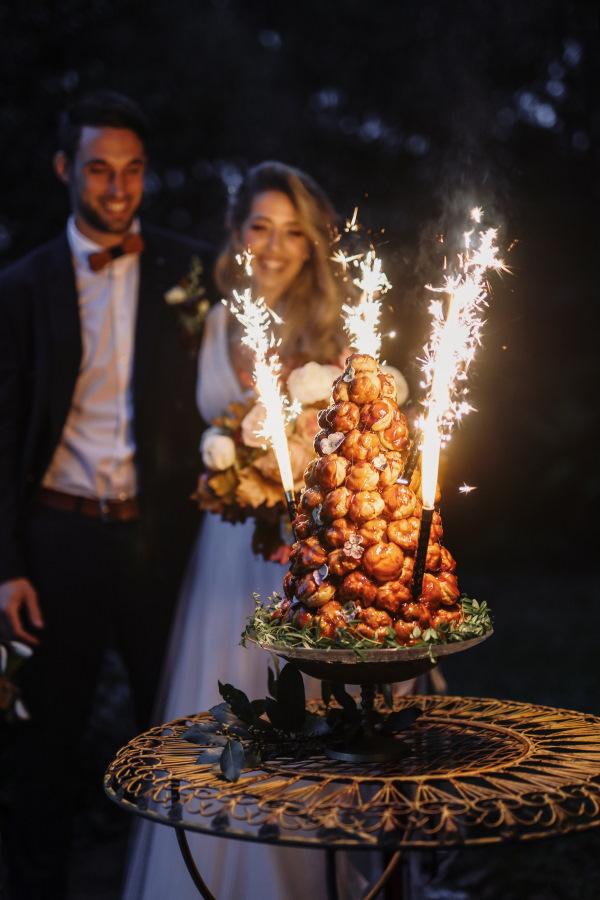 Les mariés sourient alors que les cierges s'enflamment sur leur croquembouche dans le noir