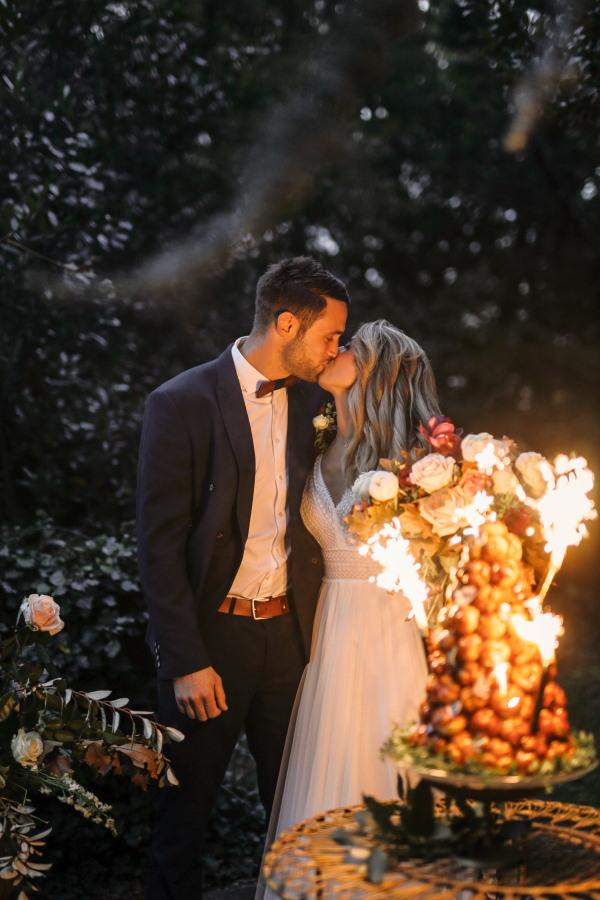 Les mariés s'embrassent dans la lumière étincelante alors qu'ils coupent leur croquembouche