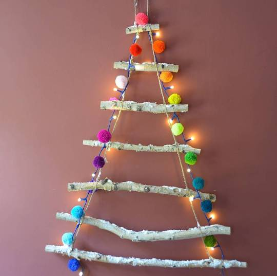 Contemporary snowy rope ladder hanging Christmas tree with lights