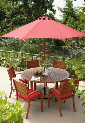 Warm red accessories teamed with wooden garden furniture helps create a Mediterranean feel
