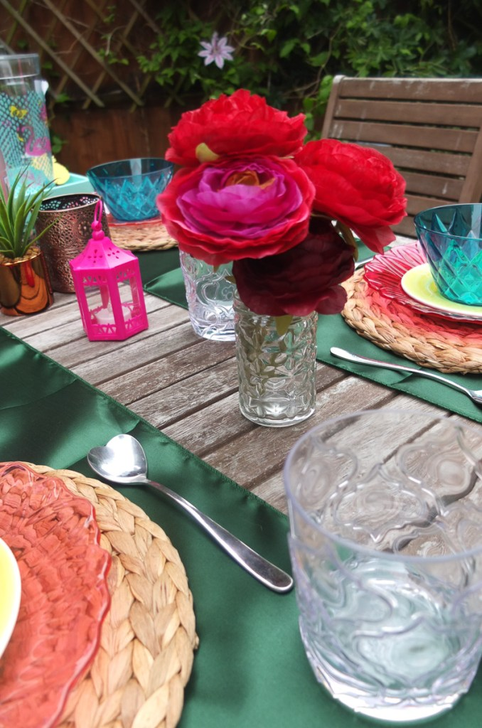 Dine outside in style with a bohemian brights pink and green colour scheme