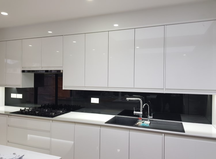 Stunning black kitchen glass splashback - it works well in contrast to white cupboards