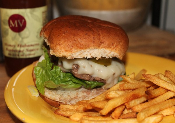 Farm-raised hamburgers with Maize Valley Honey Habanero Sauce, jalapenos, onion, lettuce and baby Swiss cheese, with a side of French fries.