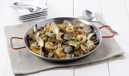 Rice in a pan with clams, shrimp, sausage, tomatoes, onion with a napkin, silverware and white plates