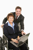 woman in wheelchair with laptop and boss standing behind