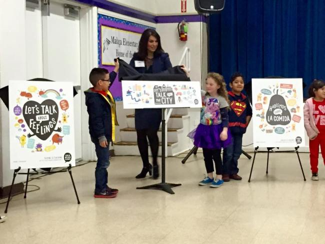 Lori Gonzalez of Fowler Unified along with students from Malaga reveal sample campaign graphics at the press event