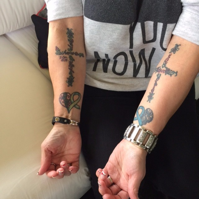 Remembrance cross and ribbon tattoos on Deborah's forearms