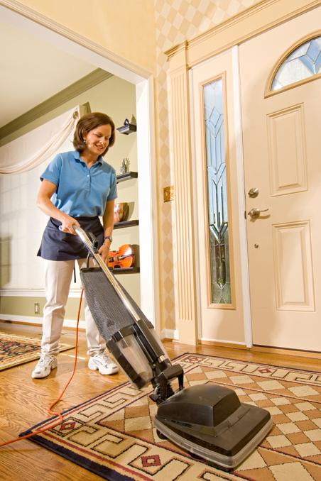 Cheerful expression worn by a well uniformed housekeeper. She is vacuuming the entry foyer into a luxury home.