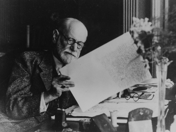 Black and white photograph of Sigmund Freud holding a sheet or writing.