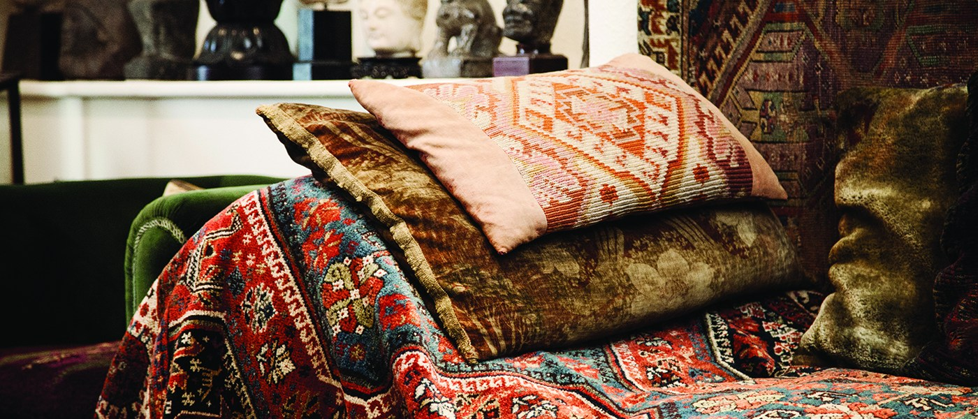 A photograph of Freud's couch which is covered in a colourful rug and cushions