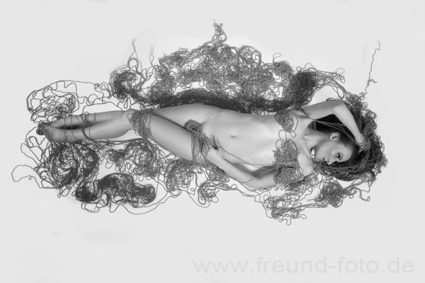 Nackte Frau liegt auf dem Boden in Baumwollte