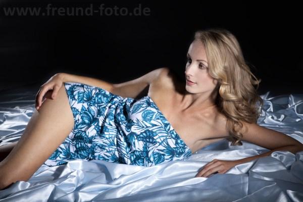Frau liegt sexy auf Bett im Fotostudio
