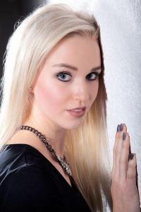 Junge blonde Frau an der Wand