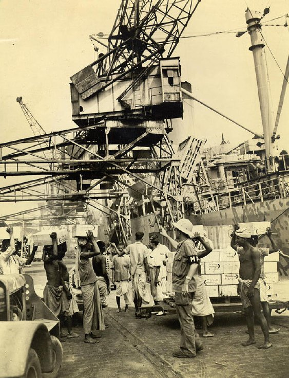 GI dock workers of the Port comapanies created order out of cahos at Calcutta's great docks and thousandsof tons of vital war supplies flowed through to china, Burma and India. The MP is on hand to see that the coolies do not pilfer from the rations they are carrying.