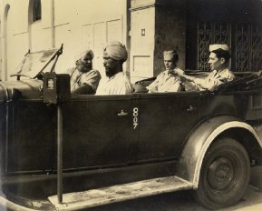 Of Calcutta's assortment of colorful and intriguing characters, the sikh taxi-driver and his co-pilot rank high. The co-pilot was added in 1944 following an affray in which a soldier knifed a driver. The two GI's shown here are doing their best to convey their destination to the driver of the ancient jalopy.