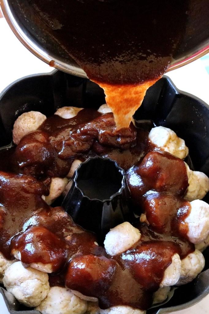 Amish Friendship Bread Monkey Bread cinnamon mixture poured over dough balls in Bundt pan | friendshipbreadkitchen.com