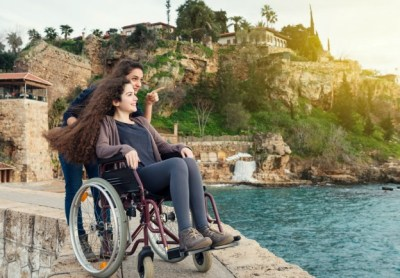 girl helping another girl in a wheelchair