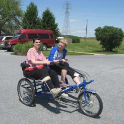 Team Member assisting an Individual on a Side By Side Tandem Tricycle