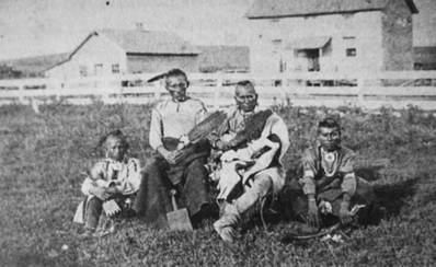 Kansa men and boys in front of the Quaker industrial boarding school (seen in background), circa 1871, near Council Grove, Kans. Courtesy of Scott Brockelman.