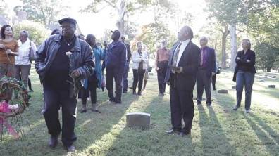 Attenders of the dedication ceremony visit the unmarked graves. From Abington Meeting's YouTube channel.