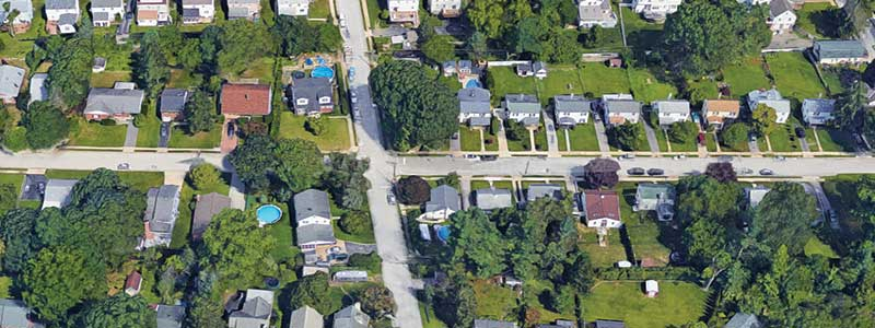 Overhead view of a city neighborhood with trees and yards.