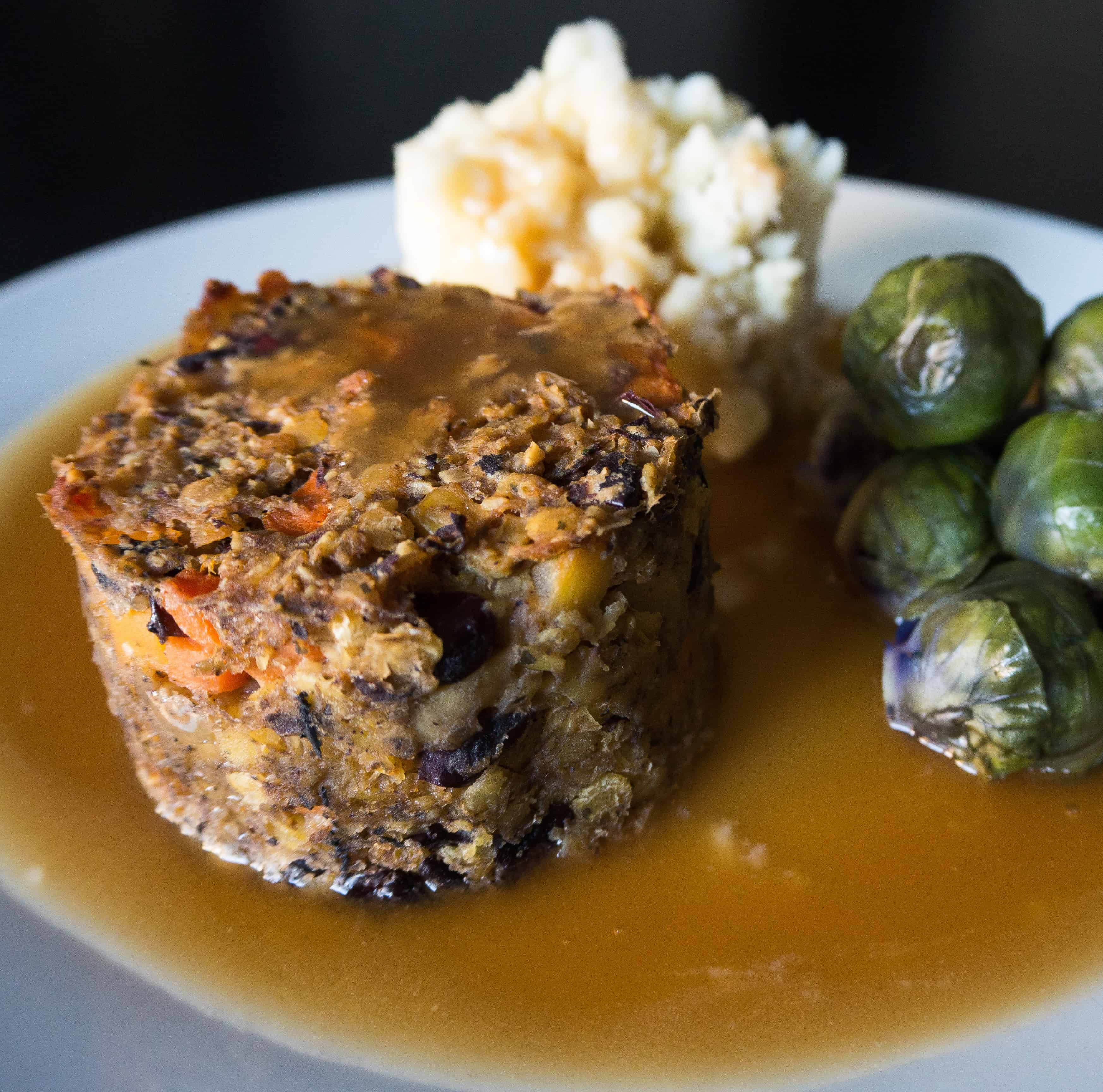 Gluten free, vegan haggis with mashed potatoes, purple sprouts and gravy