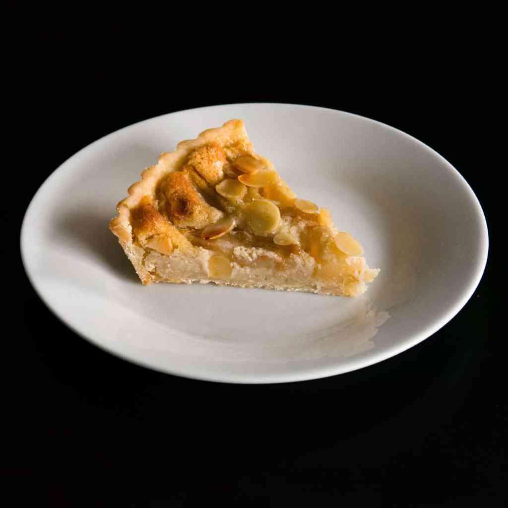 Slice of gluten free, vegan Pear Frangipane Tart. Delicious autumn dessert.