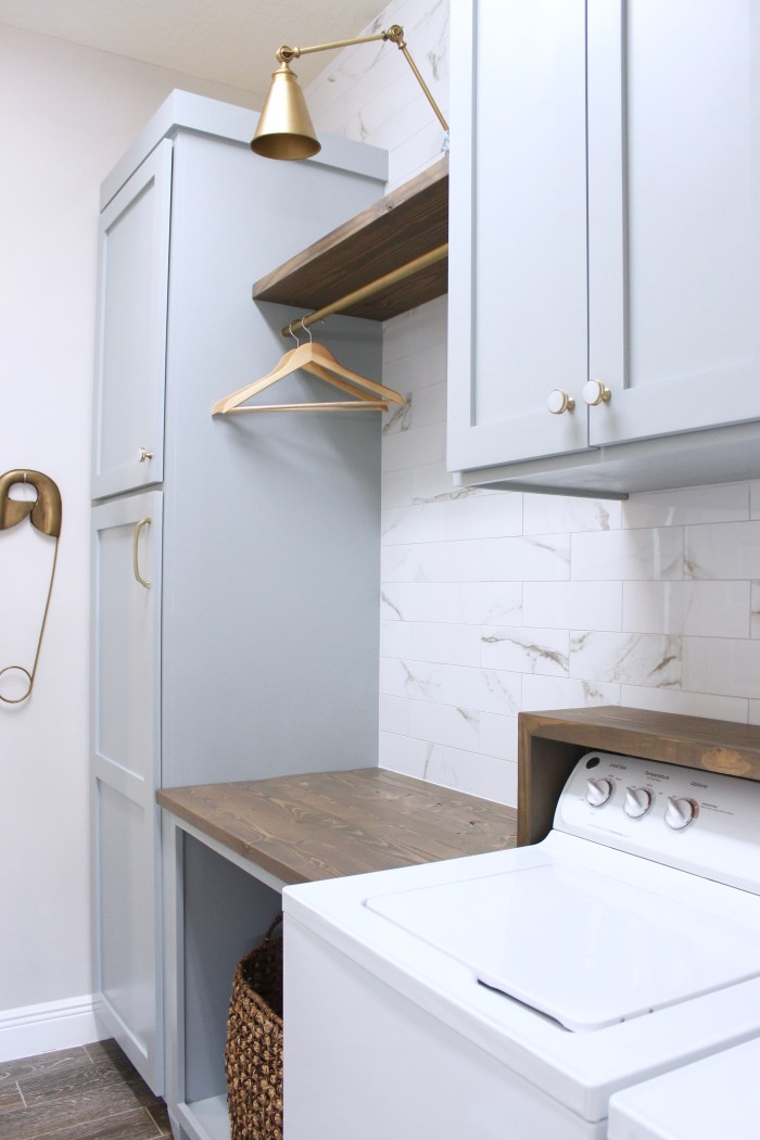 laundry room-diy-cabinets-painted-blue-marble-wall-tile-gold-sconce-light