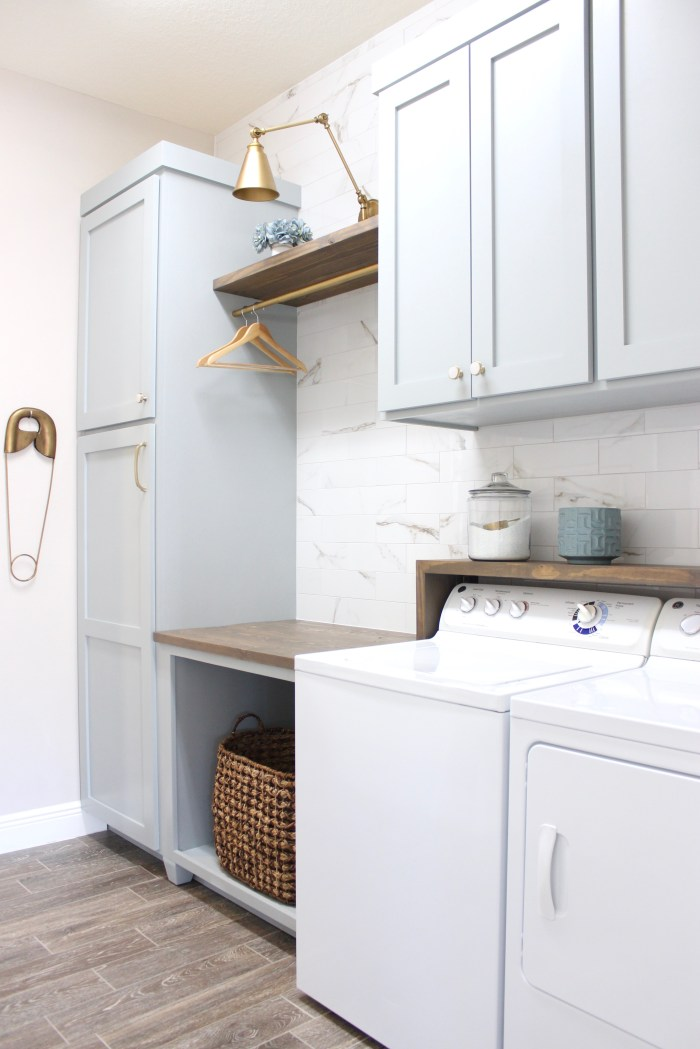 laundry room-diy-painted-blue-cabinets-marble-wall-tile-gold-sconce-light-rustic-shelf-anbove-washer-dryer