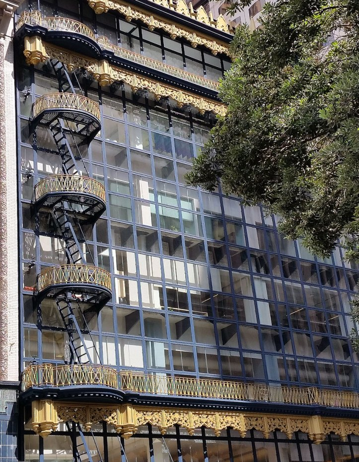 Street-level view of Hallidie Building, showing ornamented fire escapes.