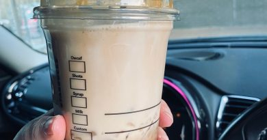 Left hand holding full iced latte in clear plastic Starbucks cup. Behind cup is dashboard of car and windscreen