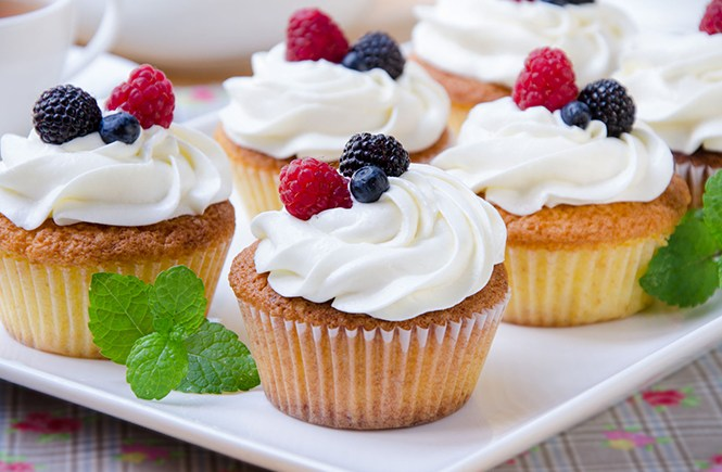 Close-up picture of a platter of vanilla cupcakes with vanilla frosting topped with fresh berries.