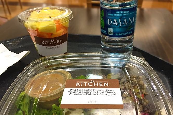Boxed salad, cup of mixed fruit, and a bottled water on a lunch tray.