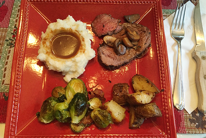 Square plate with roast, potatoes, and brussel sprouts.