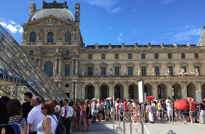 Photograph of two lines of people waiting outside to be admitted into the Louvre museum.