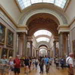 Photograph of a crowd of people looking at paintings in the Louvre.