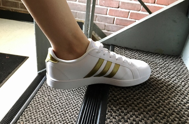 A foot wearing a white sneaker with gold stripes walking up stairs.