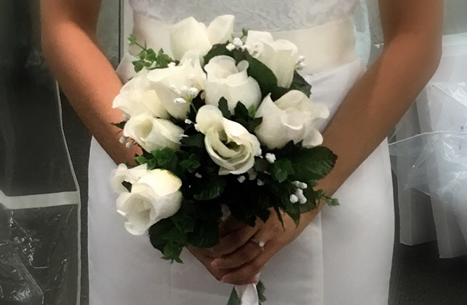 Close up photograph of me holding a white rose bridal bouquet.