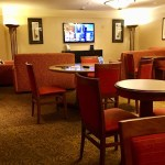 Hotel lounge with tables, chairs, couches, and a tv.