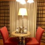 A small table with two red chairs in front of curtains.