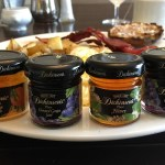 Assorted mini jars of jelly on a breakfast platter.