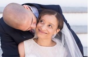 Me looking happily as my husband kisses my cheek.