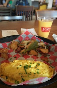 An omelette platter with breakfast potatoes and orange juice.