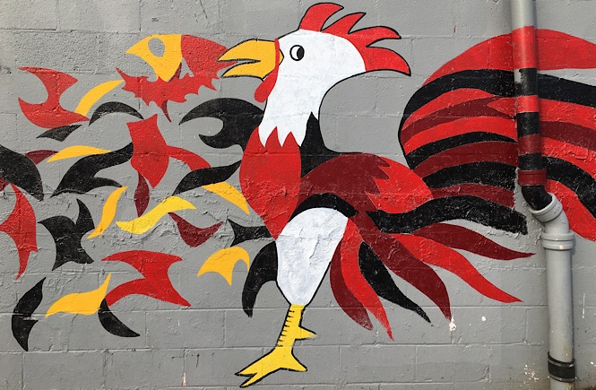 Street art of a chicken with flames on the side of a building.