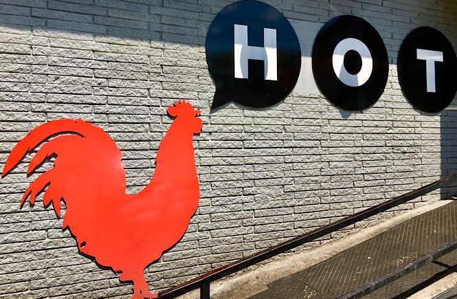 """A red chicken silhouette with the words, """"HOT"""" against a building wall."""