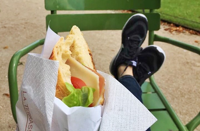Feet crossed on a chair in a park. A sandwich rests in the foreground.