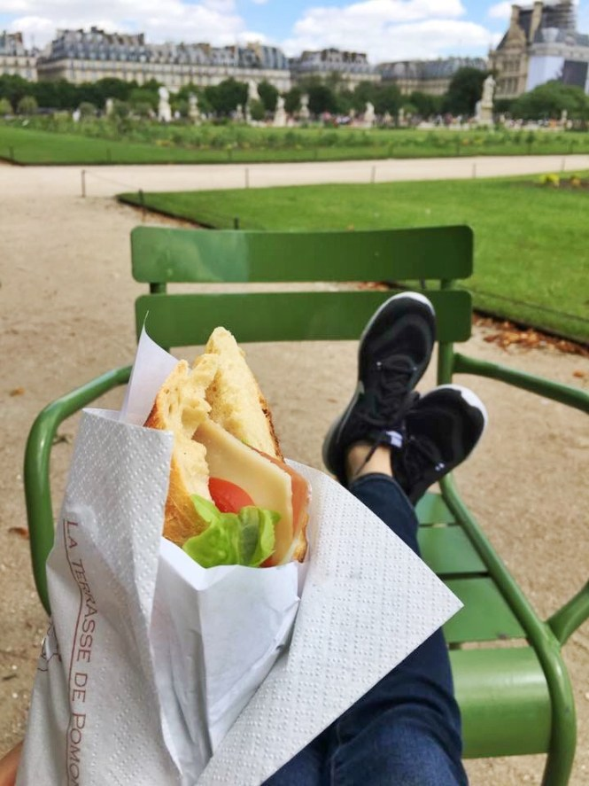 Feet crossed on a chair in the Jardin des Tuileries in Paris, France. A sandwich rests in the foreground.